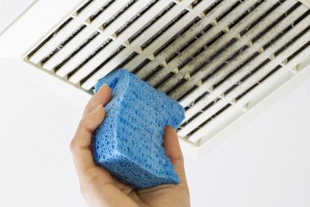 staub: Nahaufnahme horizontale Foto der weiblichen Hand Reinigung von verschmutzten Bad Lüfteröffnung Abdeckung mit blauen Schwamm