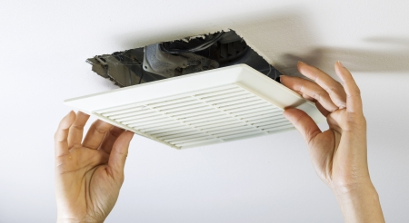 Close up horizontal photo of female hands removing bathroom fan vent cover from ceiling