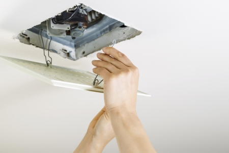 Close up horizontal photo of female hands installing clean bathroom fan vent cover from ceiling