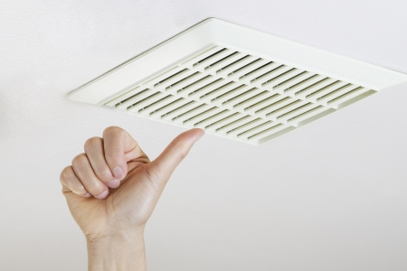 clean bathroom: Close up horizontal photo of female hand giving thumbs up after cleaning and installing bathroom fan vent cover from ceiling