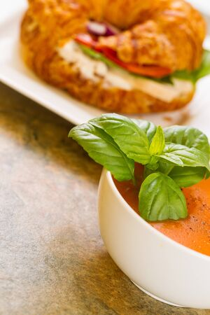 Vertical photo, slightly angled, of fresh basil in tomato soup in bowl with chicken sandwich in background all resting on natural stone counter top  photo