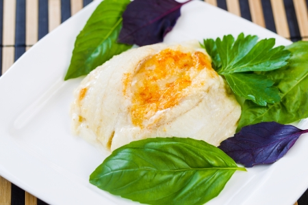 Closeup horizontal photo of baked stuffed sole fish, sweet basil, inside white square plate on bamboo placemat
