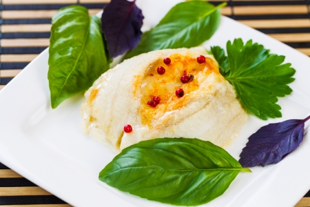 Closeup horizontal photo of baked stuffed sole fish, red peppercorn, sweet basil, inside white square plate on bamboo place mat