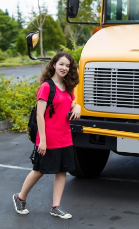 Vertical photo of young girl walking in front of bus, with back pack over her shoulders, while looking forward Stock Photo