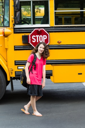 Vertical photo of young girl standing by side of school bus, with back pack over her shoulders, wearing sandals while looking forward