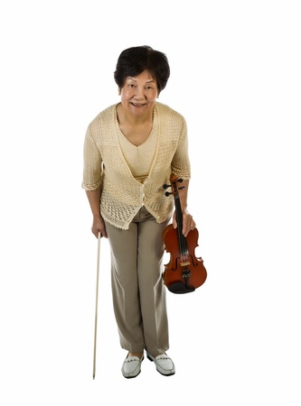 bowing: Vertical photo of a senior woman bowing after playing the violin on white background