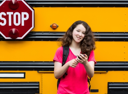 Horizontal photo of young girl standing by side of bus, with back pack over her shoulders, cell phone in hands while looking forward