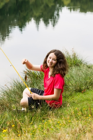 children pond: Vertical photo of young girl, looking forward, holding small fish that she caught while sitting down with lake and trees in background