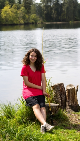 fishing bobber: Vertical photo of young girl holding fishing pole and reel, while sitting on a tree stump, with lake and trees in background