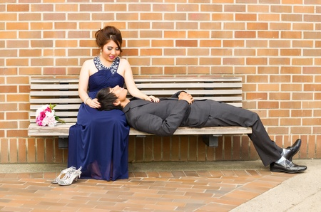 Horizontal Photo of young adult woman looking at her lover as he is lying down in her lap with brick wall in background  photo