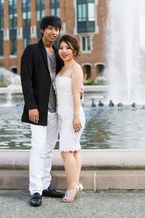 Vertical photo of young adult couple, looking forward, holding each other with water fountain, geese and brick building in background  photo