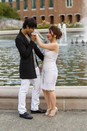 Vertical photo of young adult man kissing his lady hand with water fountain, geese and brick building in background
