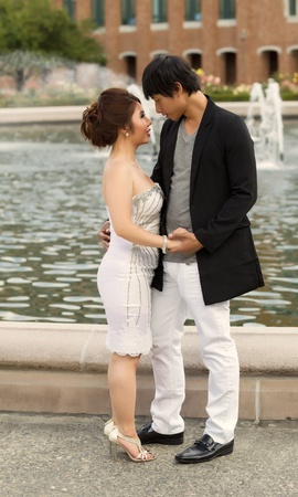 Vertical photo of young adult couple looking at each other with water fountain, flowers, trees and brick building in background  photo