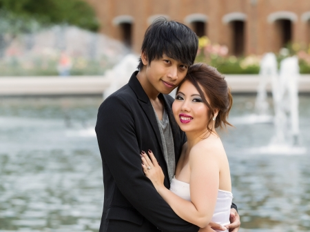 Closeup horizontal photo of young adult couple, looking forward, while holding each other with water fountain, flowers, trees and brick building in background  photo