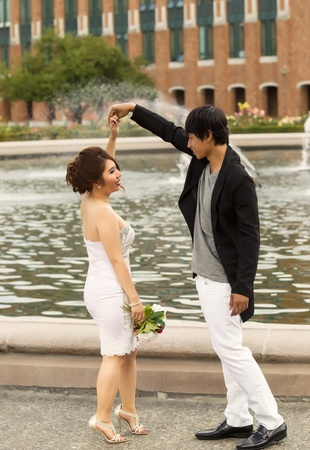Vertical photo of young adult couple, doing a twirl, while holding hands with water fountain, flowers, trees and brick building in background  photo