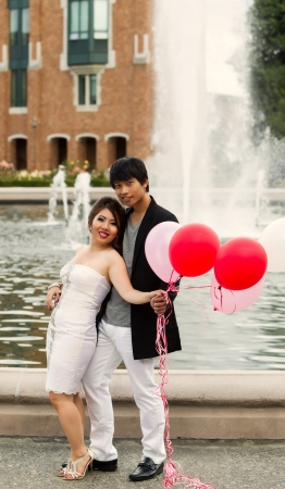 Vertical photo of young adult couple holding several balloons in front of them with water fountain, flowers, trees and brick building in background  photo