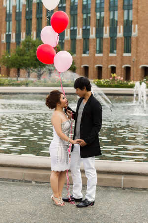 Vertical photo of young adult couple looking at each other, holding hands, with several balloons overhead of them with water fountain, flowers, trees and brick building in background  photo