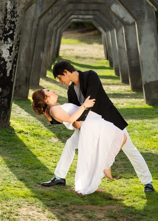 Vertical photo of young adult couple dancing outdoors together underneath a structured column wall in background  photo