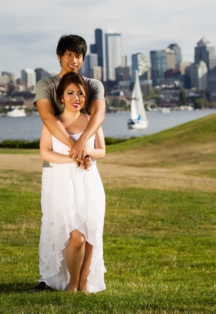 Vertical photo of young adult couple, facing forward, holding each with city of Seattle and harbor in Background photo