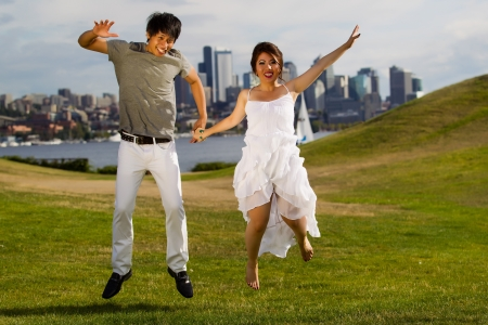 Horizontal photo of young adult couple jumping up together with city of Seattle and Puget Sound Water in Background photo