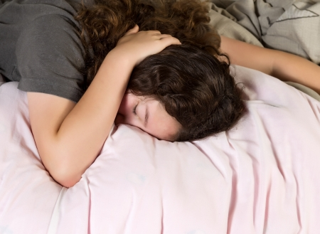 obudził: Young girl trying to wake up in the morning with hand over her head while lying in bed