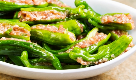 uncooked fresh, stuffed green sweet peppers in white bowl on stone counter top Stock Photo - 22478966