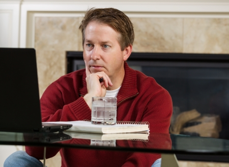 Photo of mature man, dressed casually while sitting down at glass table, working from home, looking at computer screen with fireplace in background  photo