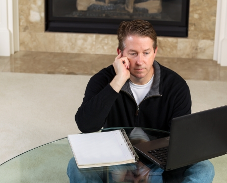 Photo of mature man, sitting down at glass table, working from home, looking at computer screen with fireplace and living room wall in background   photo