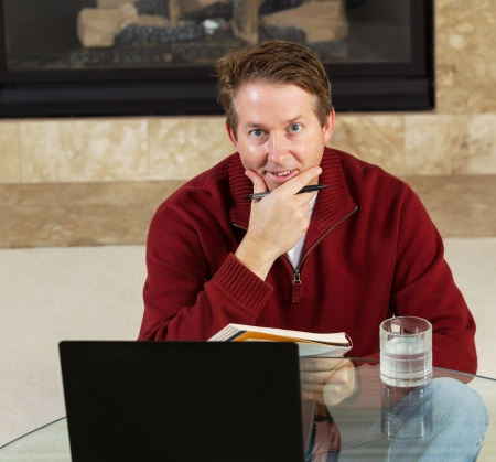 Photo of mature man, looking forward while sitting down at glass table, working from home with fireplace in background  photo