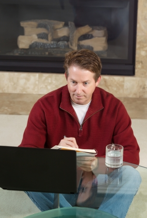 Vertical photo of mature man writing down notes from computer screen with fireplace in background  photo