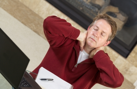 Angled horizontal photo of mature man holding his neck in hands while thinking of work with fireplace in background   photo
