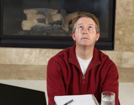 Photo of mature man looking up in frustration while work from home with fireplace in background   photo
