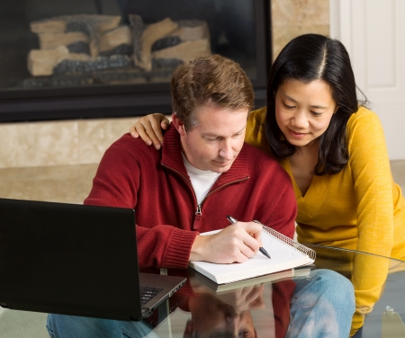 Photo of mature couple closely working together at home with fireplace in background   photo