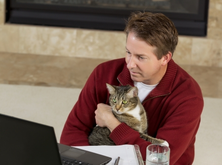 Photo of mature man reading computer screen, with family cat in his lap, while working from home with fireplace in background   photo