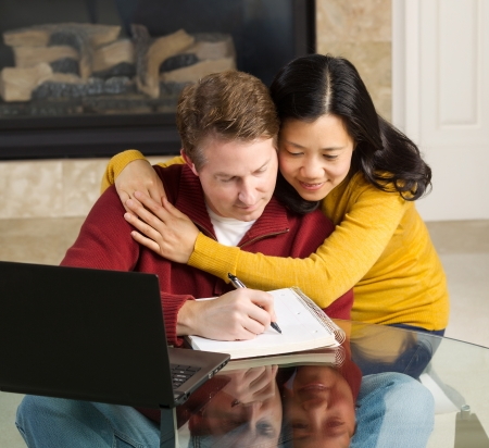 Photo of close mature couple displaying happiness while working from home with fireplace in background   photo
