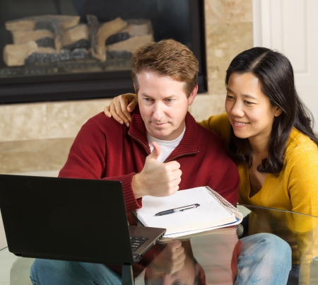 Photo of close mature couple looking at information, man giving thumbs up, on the computer screen together with fireplace in background   photo