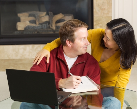 Photo of close mature couple looking at each other while working from home with fireplace in background   photo