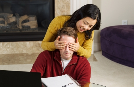 Photo of mature couple, with woman covering up the eyes of man, while working from home with fireplace and partial sofa in background   photo