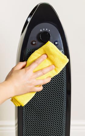 여성의 손을 배경으로 벽과 노란색 마이크로 화이블 걸레와 가정 공기 청정기를 청소
