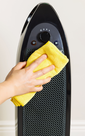 female hand cleaning home air purifier with yellow microfiber rag with wall in background  Stock Photo