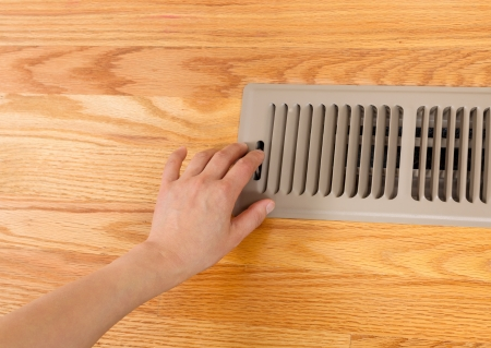 Horizontal photo of female hand opening up heater floor vent with Red Oak Floors   Stock Photo