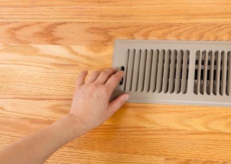 Horizontale foto van vrouwelijke hand openstelling verwarmer vloer vent met Red Oak Floors