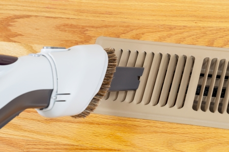 Horizontal photo of vacuum cleaning heater floor vent with Red Oak Floors in background  Banco de Imagens
