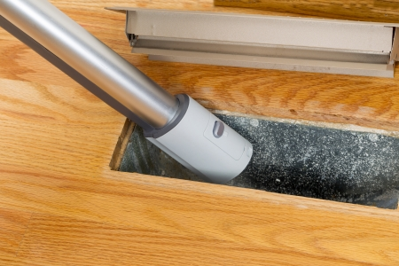 Horizontal photo of vacuum cleaning inside heater floor vent with Red Oak Floors in background