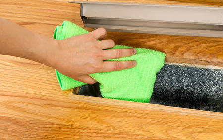 Horizontal photo of female cleaning inside heater floor vent with Red Oak Floors