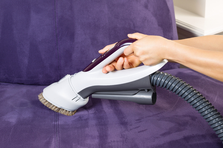 Horizontal photo of female hands holding vacuum cleaner extension for cleaning suede leather couch
