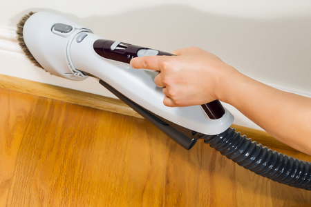 wooden floors: Horizontal photo of female hand with vacuum cleaner brush extension cleaning trim work near wooden floors