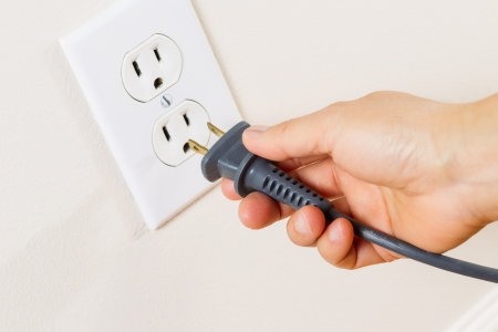 receptacle: Horizontal photo of female hand inserting power cord receptacle into electric wall outlet