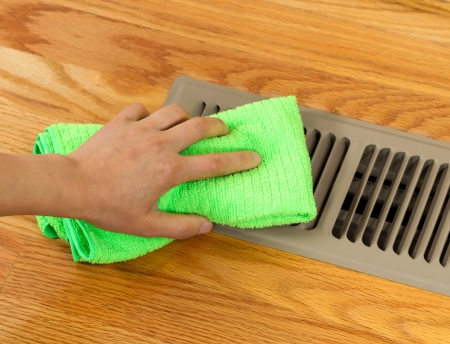 Horizontal photo of female hand cleaning outside grill plate of heater floor vent