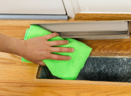 clean air: Horizontal photo of female hand cleaning, using microfiber rag, underneath grill plate of heater floor vent with Red Oak Floors and front door in background